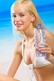 Vrouw met water op strand Stock Afbeeldingen