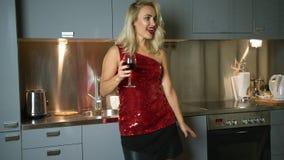 Vrouw met wijn die in keuken dansen stock videobeelden