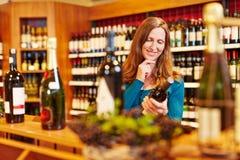Vrouw met wijnfles in organisch Stock Foto