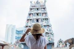 Vrouw met witte kleding reizen en hoed, gelukkige Aziatische reiziger die aan de Tempel van Sri Mariamman in Chinatown van Singap stock afbeelding