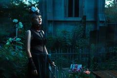 Vrouw met witte ogen die zich in een begraafplaats bij nacht bevinden royalty-vrije stock foto