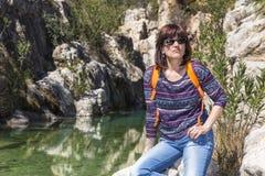 Vrouw met zonnebril die naast een rivier in de bergen rusten Royalty-vrije Stock Fotografie