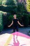 Vrouw met zwart kledingstouwtjespringen in het park Royalty-vrije Stock Afbeeldingen