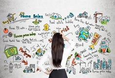 Vrouw met zwarte haar en onroerende goederenpictogrammen Stock Foto