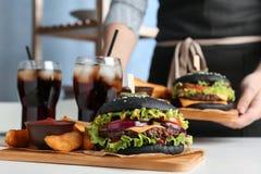 Vrouw met zwarte hamburger, gebraden gerechten en dranken die op lijst worden gediend royalty-vrije stock foto