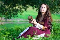 Vrouw in middeleeuws kostuum met oude kist Stock Foto's