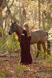 Vrouw in middeleeuwse kleding met paard in bos stock foto