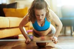 Vrouw in modern huis die opdrukoefeningen doen gebruikend saldoraad stock afbeeldingen