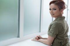 Vrouw in modieus kostuum dichtbij venster in studio Royalty-vrije Stock Afbeeldingen
