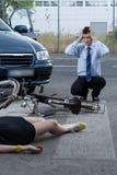 Vrouw na ongeval op fiets Stock Afbeeldingen