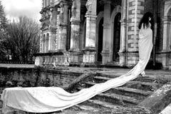 Vrouw naast oud huis Stock Afbeeldingen