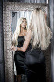 Vrouw naast spiegel Stock Foto