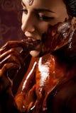 Vrouw omvat in gesmolten chocolade Stock Afbeeldingen