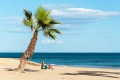 Vrouw onder de palm op het strand Royalty-vrije Stock Foto's