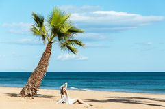 Vrouw onder de palm op het strand Stock Fotografie
