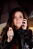 Vrouw onder paraplu op telefoon Stock Foto's