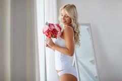Vrouw in ondergoed met bos van bloemen bij venster royalty-vrije stock afbeelding