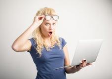 Vrouw in ongeloof die haar glazen opheffen en laptop houden royalty-vrije stock foto's