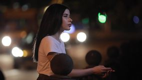 Vrouw ontspannen die zich dichtbij omheining bij nacht bevinden stock footage