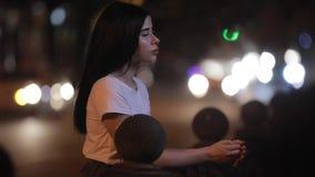 Vrouw ontspannen die zich dichtbij omheining bij nacht bevindt stock video