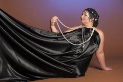 Vrouw in oosterse robes in zwarte met parels stock fotografie