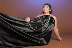 Vrouw in oosterse robes in zwarte met parels stock afbeeldingen