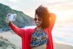 Vrouw op autoreis die selfie foto met mobiele telefoon neemt tegen het overzees stock fotografie