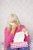 Vrouw op bed blazende neus Stock Fotografie