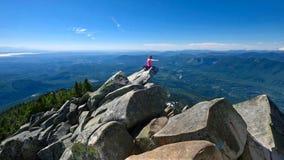 Vrouw op bergbovenkant die boven mooie mening mediteren stock afbeeldingen
