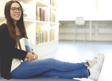 Vrouw op bibliotheekvloer wordt gezeten met rechte benen dat Royalty-vrije Stock Afbeelding