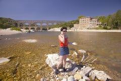Vrouw op celtelefoon bij de Rivier Gard en Pont du Gard, Nîmes, Frankrijk Stock Fotografie