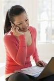 Vrouw op celtelefoon en laptop Stock Foto's