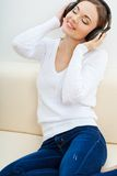 Vrouw op de bank die aan muziek luistert Stock Foto's