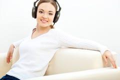 Vrouw op de bank die aan muziek luistert Royalty-vrije Stock Foto's