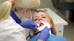 Vrouw op de inspectie van de tanden in tandheelkunde stock video