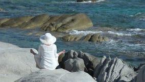 Vrouw op de rots dichtbij het overzees stock footage