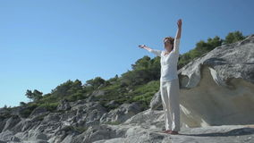Vrouw op de rots dichtbij het overzees stock video