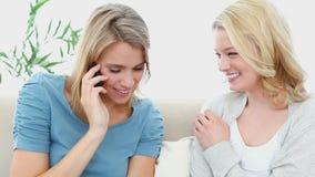 Vrouw op de telefoon die met een vriend lachen stock videobeelden