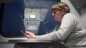 Vrouw op de trein die op de telefoon spreken stock videobeelden