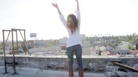 Vrouw op een dak met haar wapens wijd het open kijken stock videobeelden