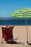 Vrouw op een deckchair bij het strand Stock Afbeelding