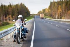 Vrouw op een motorfiets die op de kant van de weg van een weg van het land met lege weg rusten Stock Fotografie