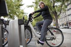 Vrouw op een openbare fiets Stock Foto's