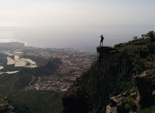 Vrouw op een rand van een berg die vallei van mening genieten Royalty-vrije Stock Foto