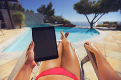 Vrouw op een zitkamerstoel die tabletpc met behulp van dichtbij de pool stock foto