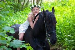 Vrouw op een zwart paard Stock Afbeeldingen