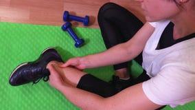 Vrouw op geschiktheidsmat met pijnlijk been Hoogste mening stock video