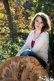 Vrouw op gevallen boom, de herfst stock foto