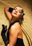 Vrouw op gouden stof Stock Foto