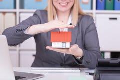 Vrouw op het kantoor die een miniatuurhuis houden Bedrijfsconcept voor bescherming, verzekering en onroerende goederen royalty-vrije stock foto's